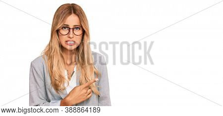 Beautiful blonde young woman wearing business clothes pointing aside worried and nervous with forefinger, concerned and surprised expression