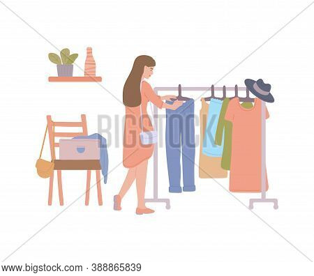 Woman At Fashion Thrift Shop Choosing Second Hand Clothes From Rack.