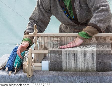 A Woman In A Gray Linen Dress Works On An Antique Wooden Loom. Historical Reconstruction Of Hand-wea