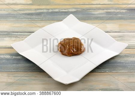 Creole Praline Caramel And Pecan Cluster On White Snack Plate On Table
