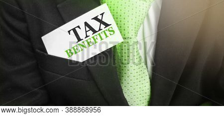 Businessman Keeps A Card With Text Tax Benefits In Upper Pocket Of His Suit. Taxes And Fees Concept