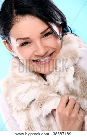 Beautifull smiling young girl in fur isolated on a blue
