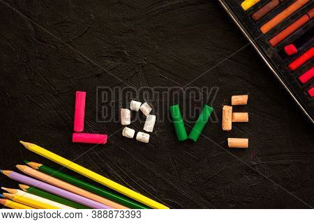 Multi-colored Pastel Crayons On A Black Background. The Word Love Is Made Of Crayons. A Symbol Of Lo