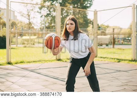 Young Cute Teen Girl Leads The Ball In A Basketball Game. A Girl Plays Basketball After School. Spor