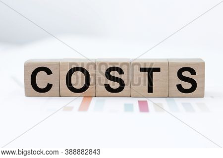 Cost, Expense Or Company Profit And Loss Concept, Cube Wooden Block With Alphabet Combine Word Costs
