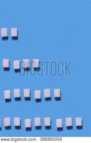 Sugar Cubes Pattern. Repetition Of Rows Of White Sugar Cubes Of Different Lengths On A Blue Backgrou