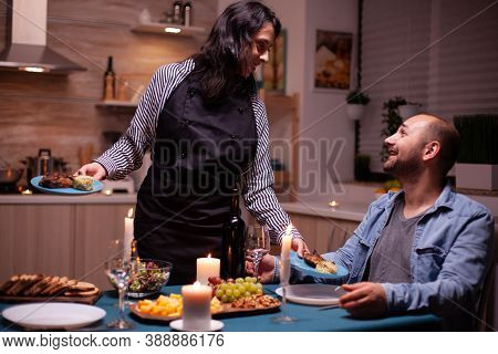 Couple Celebrating Relationship With Romantic Dinner In Dining Room. Woman Preparing Festive Dinner