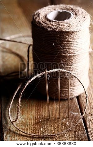 Artistic image of spool of thread and needle over wooden surface