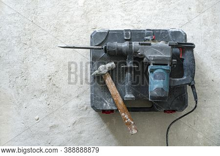 Dismanting Concept. Rotary Hammer For Construction Destroying And Hand Hammer On The Concrete Backgr