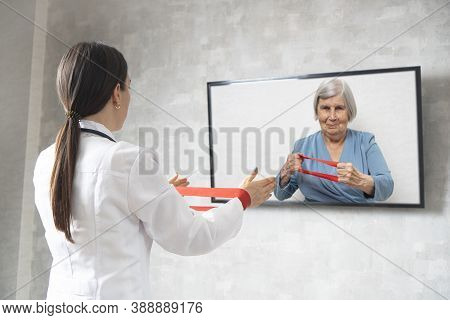 Online Physiotherapy For The Elderly. Doctor Showing An Elderly Woman Exercises With A Fitness Rubbe