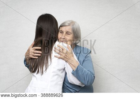 Taking Care For The Elderly. Young Doctor Hugs An Elderly Woman. They Are Happy To See Each Other. Y