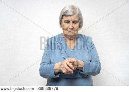 Elderly Woman Massages A Painful Palms. Senior Old Lady Has A Joints Pain In A Hands.