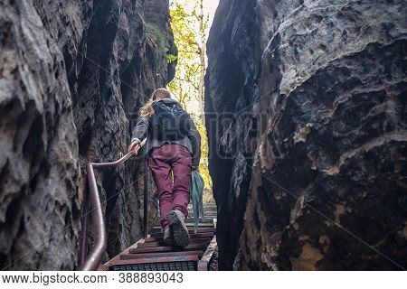 Woman Climbs The Stairs Through A Rift In The Rocks, Tisa Rocks, Czech Republic