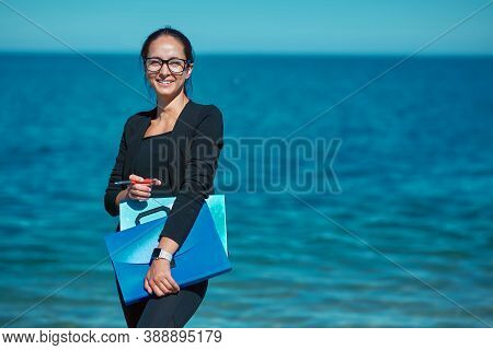 Freelance Job Remote Office And Travel Idea. Lady Carry Folders With Docs. Sea View On Backdrop. Wor