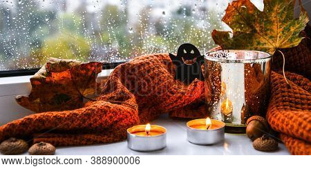 Candles With Sweater And Ghost Pumpkin, Dried Leaves On Windowsill. Halloween Home Decoration. Rainy