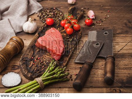 Slice Of Raw Beef Sirlion Steak On Wooden Chopping Board With Tomatoes,garlic And Asparagus Tips And