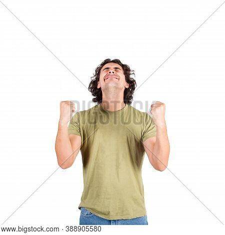 Thankful And Pleased Young Man, Long Curly Hair Style, Keeps Fists Tight Raised Up, Eyes Closed, Con