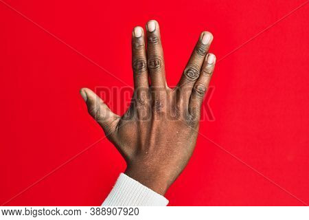 Arm and hand of african american black young man over red isolated background greeting doing vulcan salute, showing back of the hand and fingers, freak culture