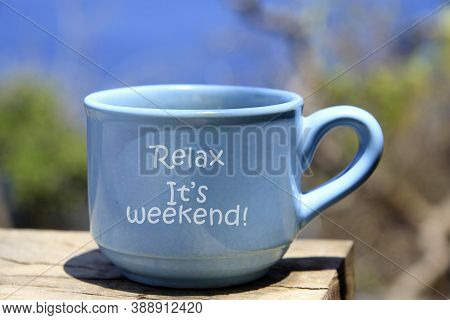 A Cup Of Coffee With Text Message On It - Relax, It Is Weekend. Coffee Cup On Wooden Rustic Table On