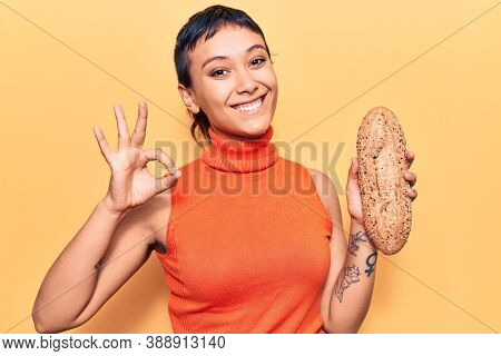 Young woman holding wholemeal bread doing ok sign with fingers, smiling friendly gesturing excellent symbol