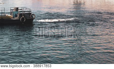 Water Surface With Ripples And Part Of A Ship. Abstract Background