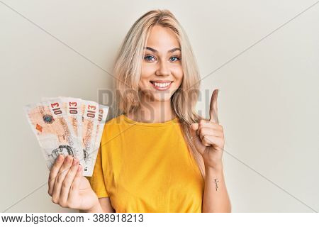 Beautiful caucasian blonde girl holding 10 united kingdom pounds banknotes smiling with an idea or question pointing finger with happy face, number one