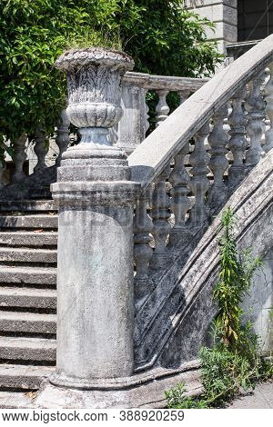 Stone Pot As A Decorative Element Of An Ancient Staircase With Stone Balusters On A Background Of Gr