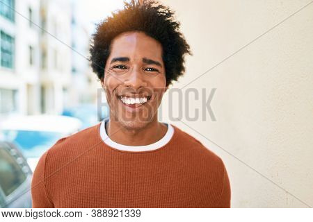 Young handsome african american man wearing casual clothes smiling happy. Standing with smile on face walking at town street.