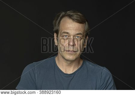 Portrait Of A Man In A Studio 40-50 Years Old In A Blue T-shirt On A Black Blurry Background, Close-