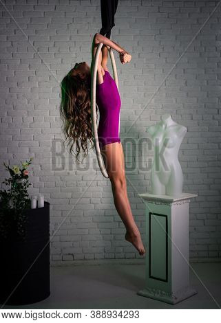 Young Girl, Gymnast. Performs Exercises On The Gymnastic Circle.