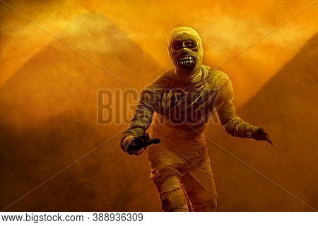 Scary evil mummy against the background of the Egyptian pyramids. Halloween. Ancient Egyptian mythology.