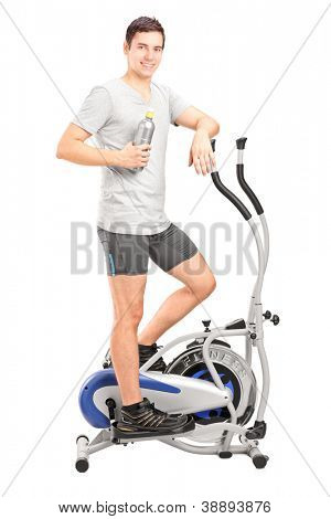 Full length portrait of an athlete standing on a cross trainer machine and drinking water isolated on white background
