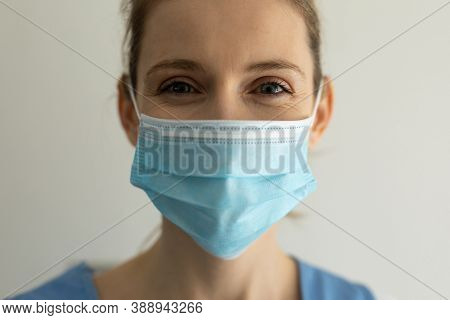 Portrait of Caucasian female nurse, wearing a face mask. Medical care at home during Covid 19 Coronavirus quarantine