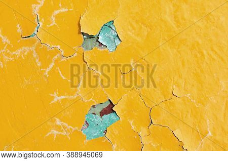 Texture background of bright yellow and blue peeling paint on the old rough concrete surface. Texture background of peeling paint, peeling paint on the texture surface, close up of peeling paint texture on the texture background. Texture surface