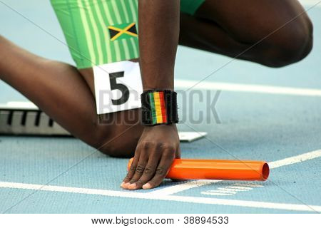 Athlete with a baton on the start of relay event