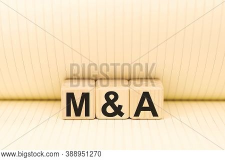 Word M And A Merger And Acquisitio On Wooden Blocks On Paper Background Top View