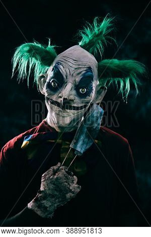 closeup of a disturbing evil clown, with green hair, wearing a dirty red costume, a dirty bow tie, and dirty and bloody gloves, putting on or taking off a nasty face mask, against a black background