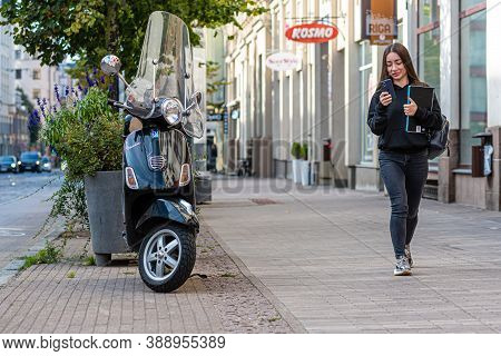 Riga, Latvia - October 8, 2020: Black Classic Vespa Scooter Parked On A Pedestrian Sidewalk In The C