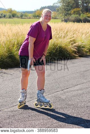 Lonely woman with mask rollerblading. People in coronavirus time. Social distancing and infection prevention.