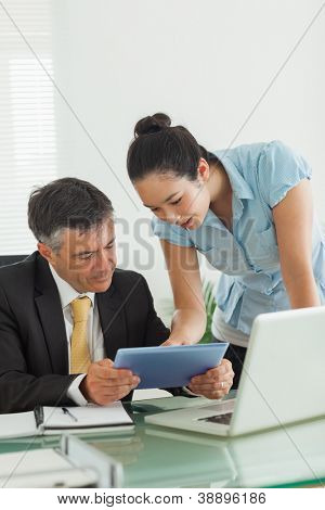 Man and woman working together on a digital tablet and a laptop in an office
