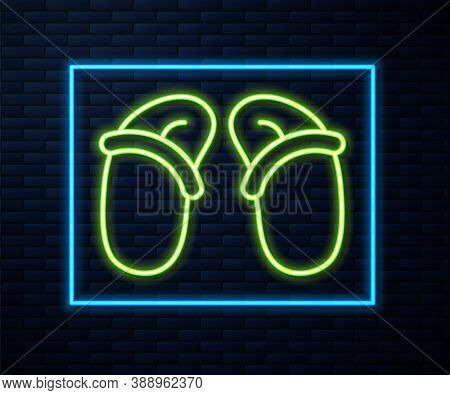 Glowing Neon Line Flip Flops Icon Isolated On Brick Wall Background. Beach Slippers Sign. Vector