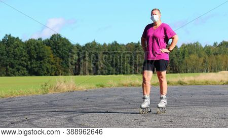 Lonely woman in mask rollerblading. People in coronavirus time. Social distancing and infection prevention.
