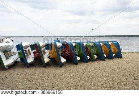 Catamarans On The Shore Are Stacked In A Row. The Sea Season Has Not Begun. Many Shore Catamarans Ar