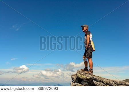 A Man Stands On The Edge Of A Stone On One Of The Peaks Of The Ukrainian Carpathians, The Montenegri