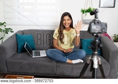 Cute Hispanic Influencer And Video Blogger Saying Hello With Hand Gesture And A Smile To Her Online