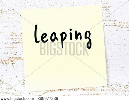 Concept Of Reminder About Leaping. Yellow Sticky Sheet Of Paper On Wooden Wall With Inscription