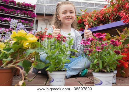 Little girl sitting on the floor and showing thumbs up and smiling in garden center