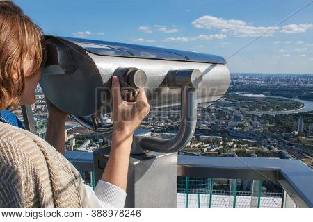 Woman On The Observation Deck , Moscow City Panorama. Woman Looks Binoculars At The City On The Obse