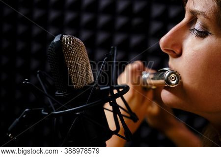 Woman Flute In Headphones Player Plays In Recording Studio, Close-up. Record Wind Musical Instrument