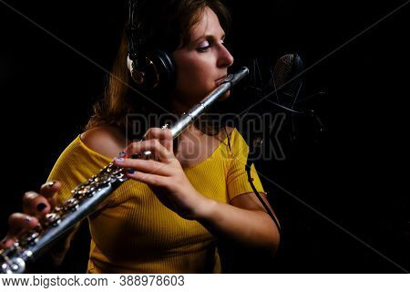 Woman Flute In Headphones Player Plays In Recording Studio. Record Wind Musical Instruments With A P